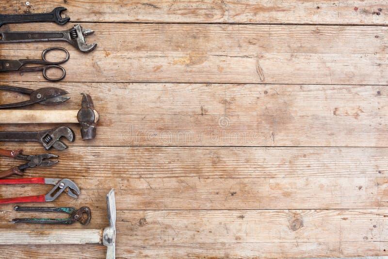 建筑工具的构成工具老被打击的木表面上的:钳子,管扳手,螺丝刀,锤子,金属牛油树 免版税库存图片
