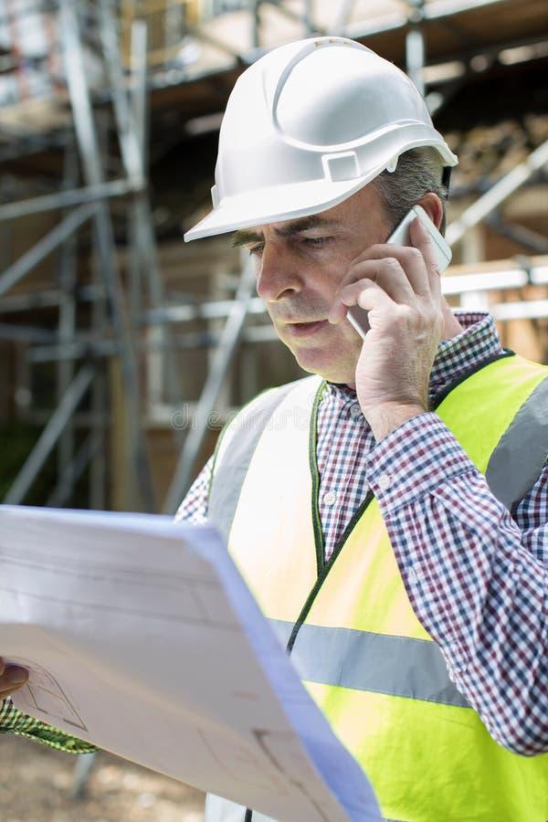 建筑工地的建筑师使用手机 免版税库存照片