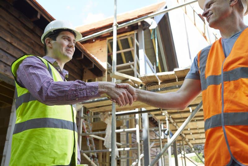 建筑师与有建造者的握手 图库摄影