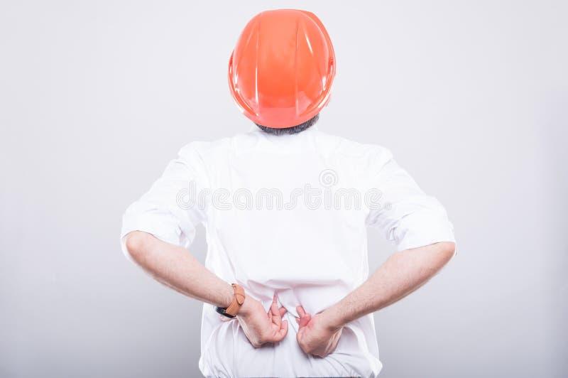 建筑师佩带的安全帽后面看法遭受背部疼痛的 库存图片