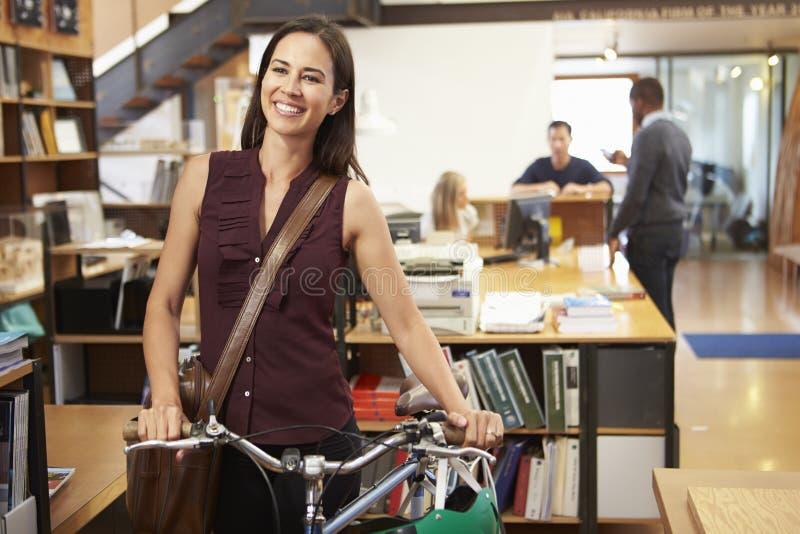 建筑师到达在穿过它的自行车的工作办公室 免版税库存照片