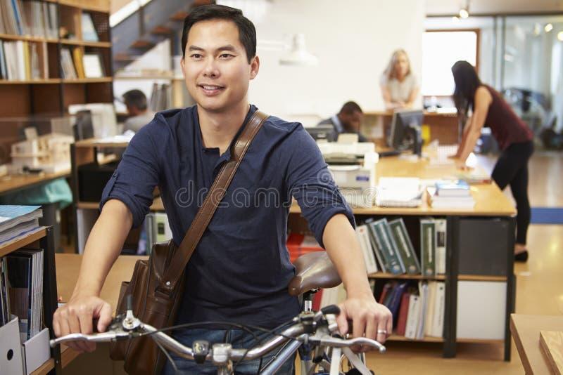 建筑师到达在穿过它的自行车的工作办公室 免版税图库摄影