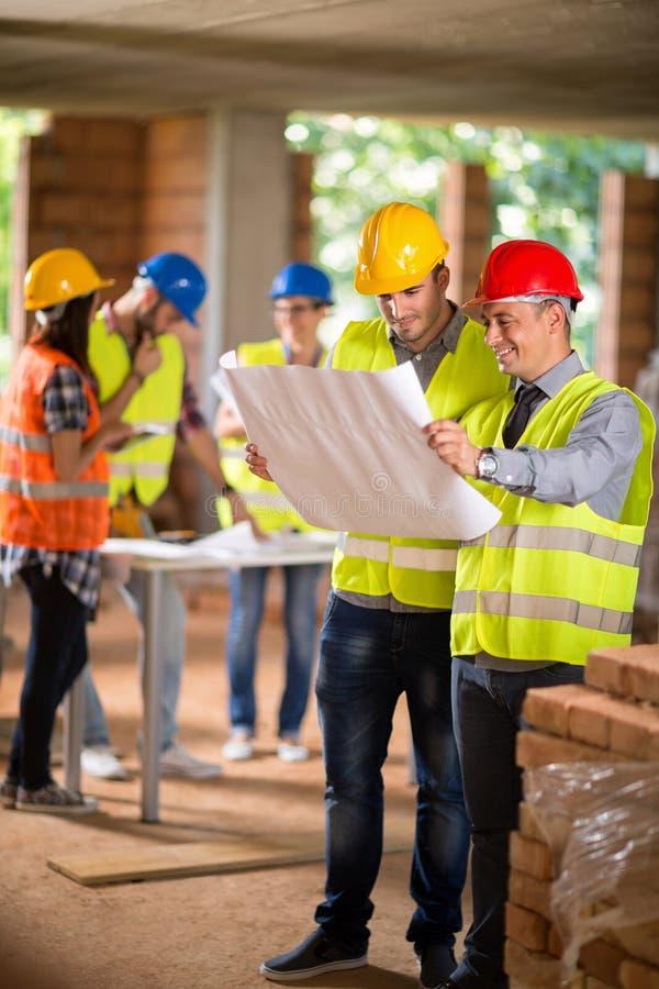 建筑师和建筑工人看起来方案 库存照片
