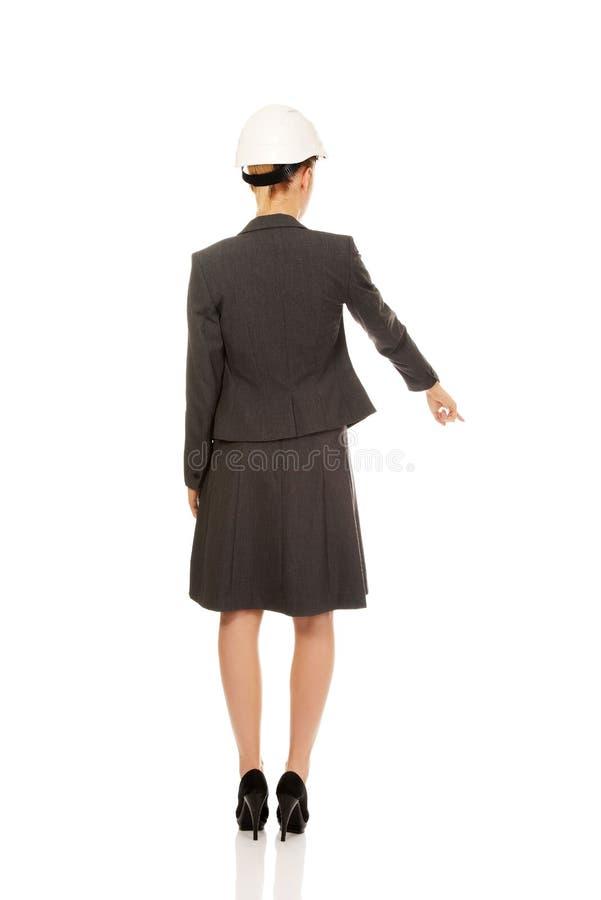 建筑师女商人佩带的白色的盔甲Backview指向下来 免版税图库摄影