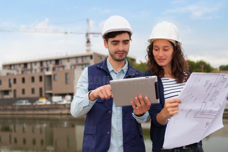 建筑师妇女和建造场所监督员 免版税库存照片