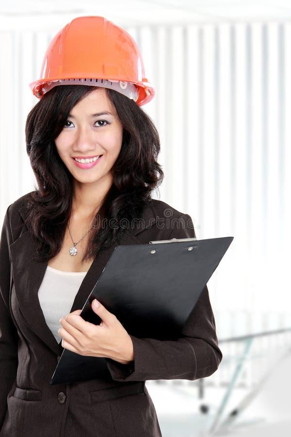 建筑师盔甲橙色妇女年轻人 免版税库存图片