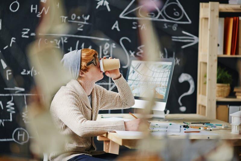 年轻建筑师饮用的咖啡,当工作时 库存照片