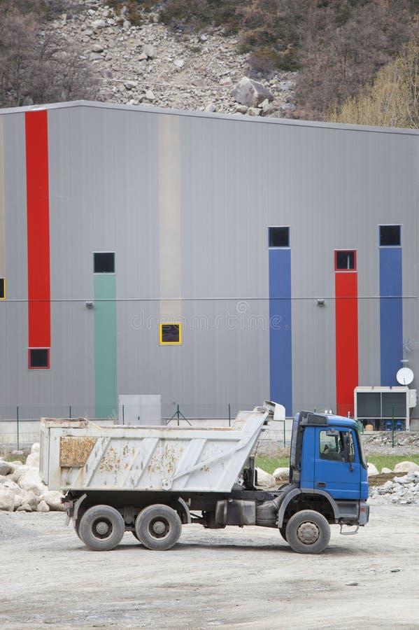 建筑材料的运输的卡车 放置户外站点的砖建筑 免版税库存照片