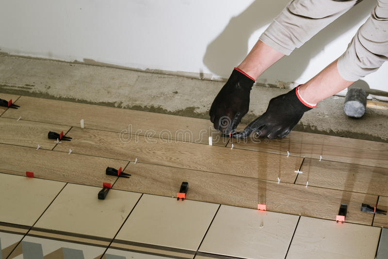 建筑泥工在瓦片的人手与水泥灰浆一起使用 免版税图库摄影
