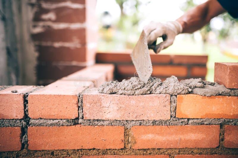 建筑瓦工工作者有砖、灰浆和油灰刀的大厦墙壁 免版税库存图片