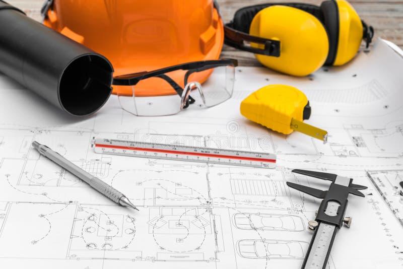 建筑计划与盔甲和绘图工具在图纸 免版税库存照片