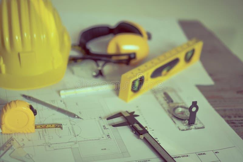 建筑计划与盔甲和绘图工具在图纸 免版税库存图片