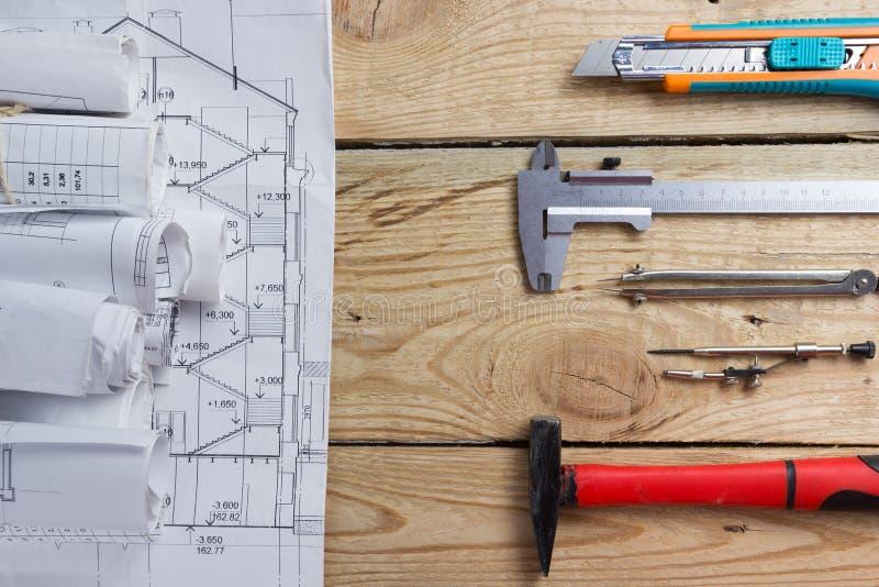 建筑项目、图纸、图纸卷和分切器指南针,在葡萄酒木背景的轮尺 建筑concep 库存图片
