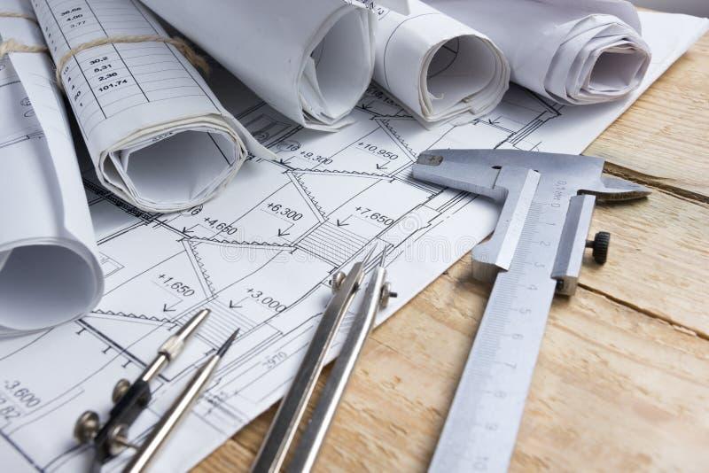 建筑项目、图纸、图纸卷和分切器指南针,在葡萄酒木背景的轮尺 建筑concep 免版税库存照片
