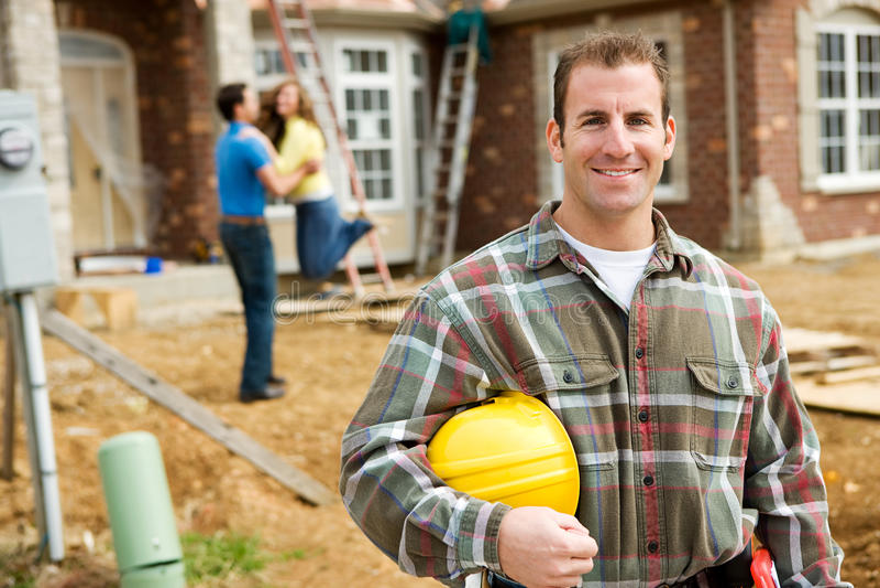 建筑:与激动的房主的承包商在背景中 免版税库存照片