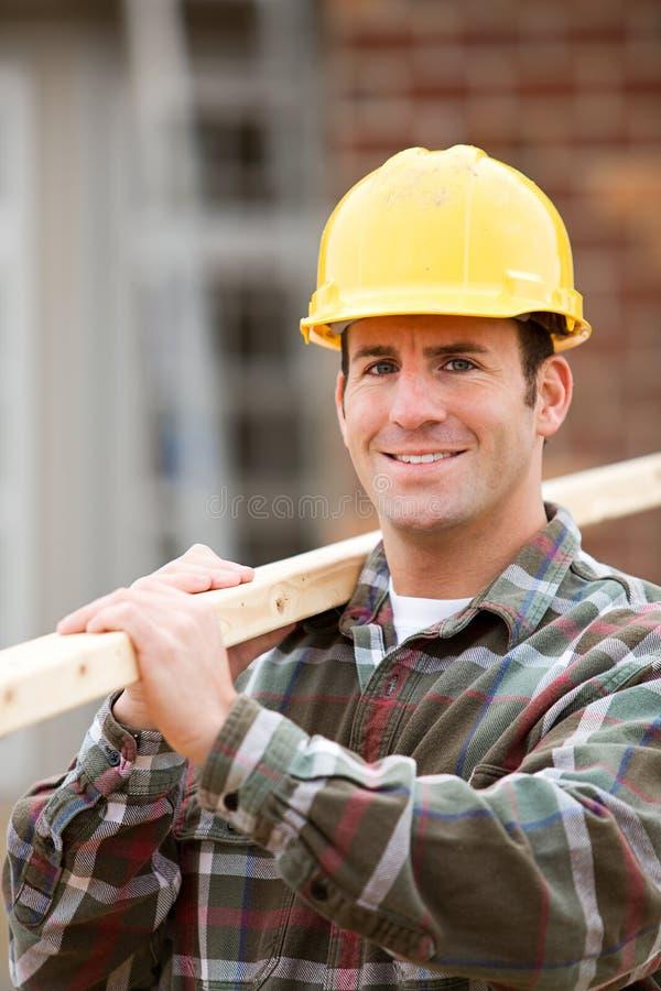 建筑:工作者站立与在肩膀的2x4 免版税库存图片