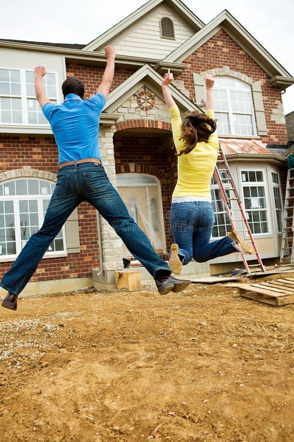 建筑:年轻夫妇在兴奋跳跃 免版税库存图片