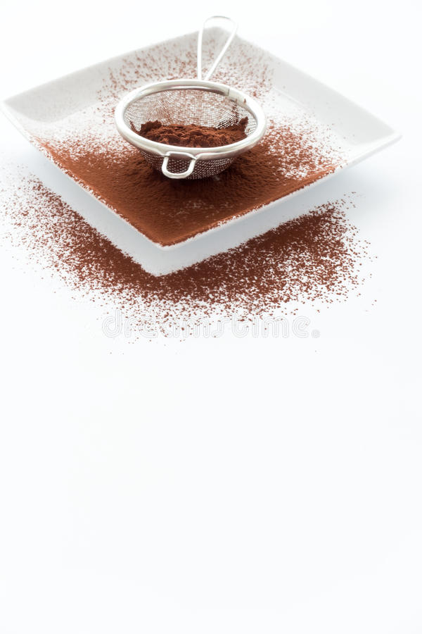 筛子用在瓷板材和白色后面的可可粉填装了 库存图片