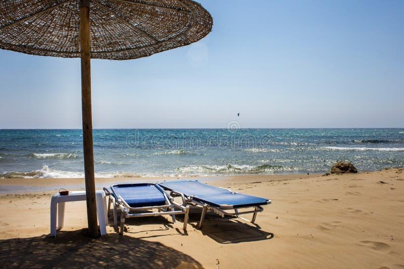 筛选阳光和热的木伞 面对海洋的被折叠的和展开的可调整的海滩可躺式椅 好 免版税库存照片