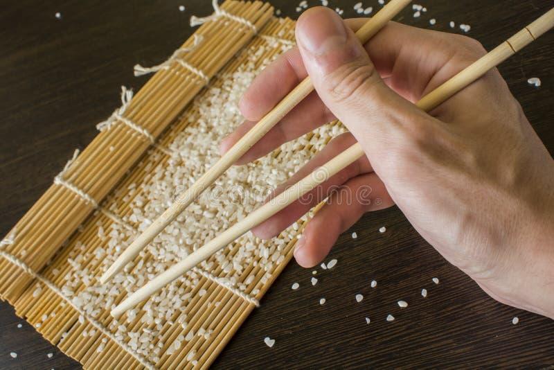 筷子在手中在寿司席子和疏散米的背景中 免版税图库摄影