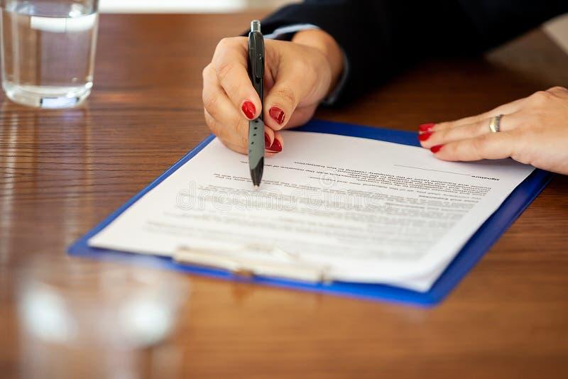 签一个合同的女实业家的手在meetinf屋子 库存图片