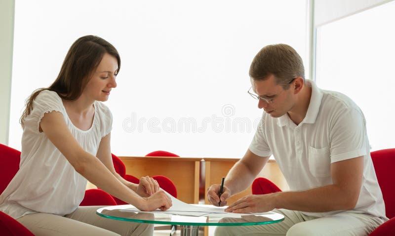 签合同的微笑的年轻商人 免版税图库摄影