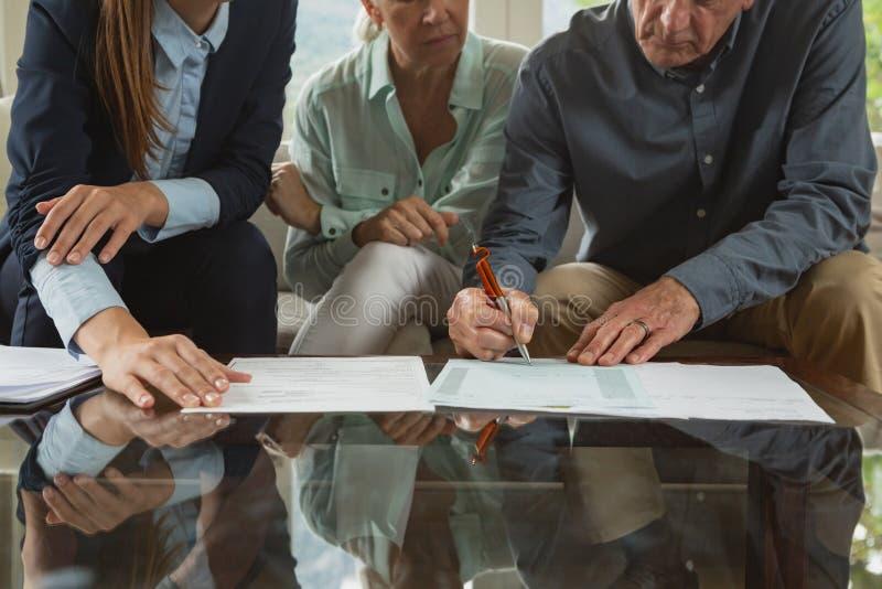 签署一个合约与在文件的不动产房地产经纪商的活跃资深夫妇在客厅 免版税库存照片