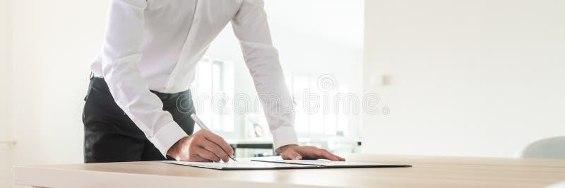 签署文件的商人的宽看法图象 免版税库存照片