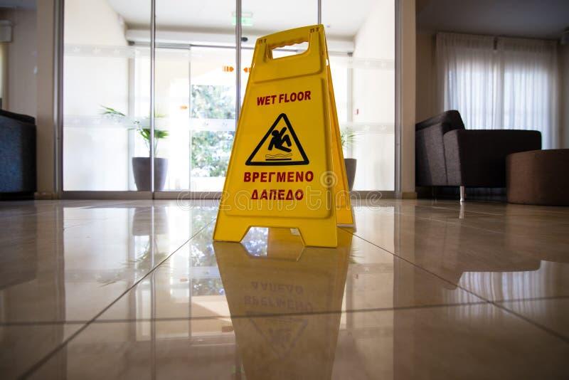 签署显示警告在湿砖地上的小心湿地板在日落 库存图片