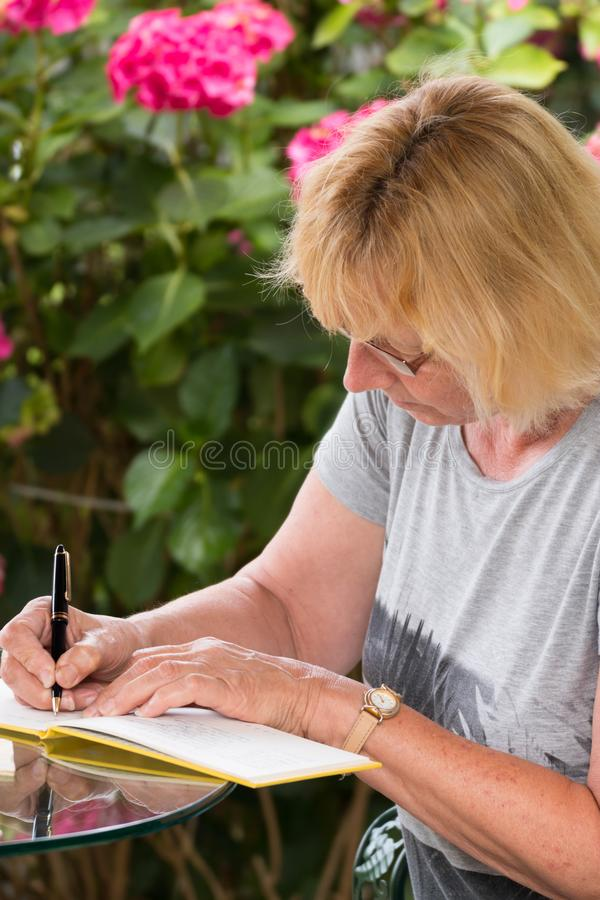 签署留言簿的成熟妇女 免版税库存图片