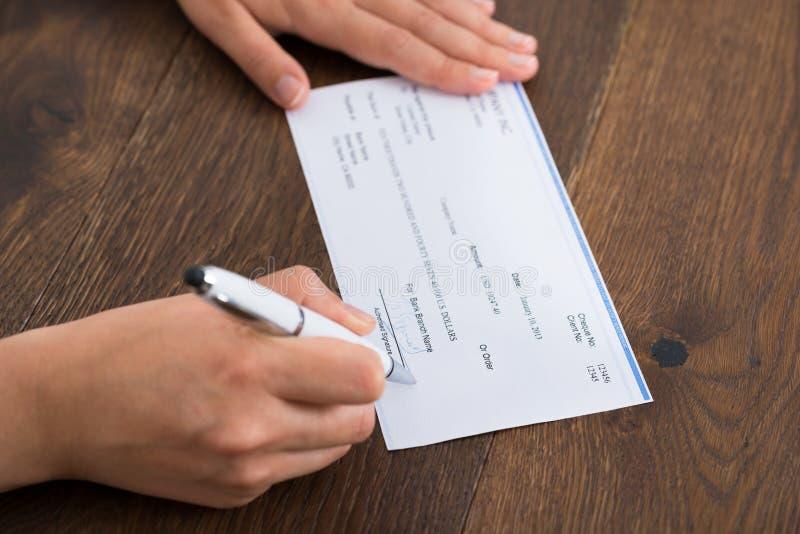 签署钞票的人手 免版税图库摄影