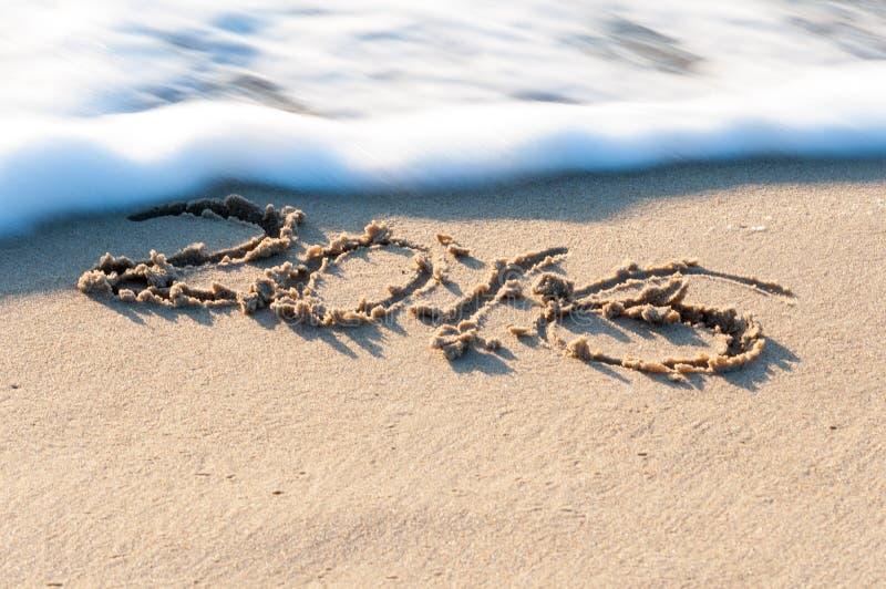 签署2016年在海滩沙子,波浪几乎报道数字 夏天旅行概念 免版税图库摄影