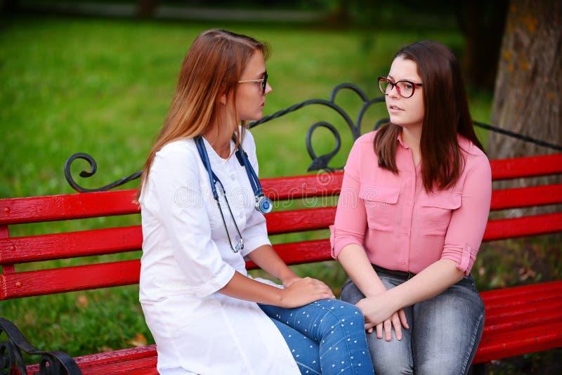 简单的交谈 采取年轻患者的关心的医生或护士 图库摄影