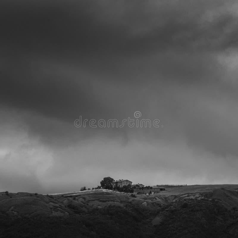 简单的房子的艺术性的黑白图象小山的在托斯卡纳,意大利 库存照片