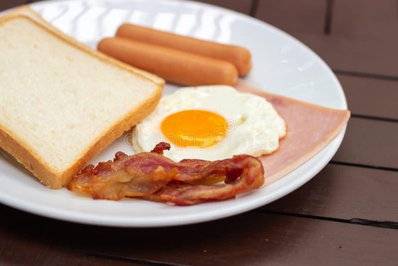 简单的早餐多士面包、荷包蛋、香肠、火腿和烟肉 库存图片