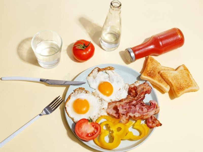 简单的早餐荷包蛋用烟肉、甜椒和多士在板材 图库摄影