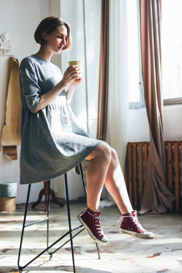 简单的灰色礼服的年轻女人有黄色杯子的坐椅子在书刊上的图片演播室,全长画象 库存照片