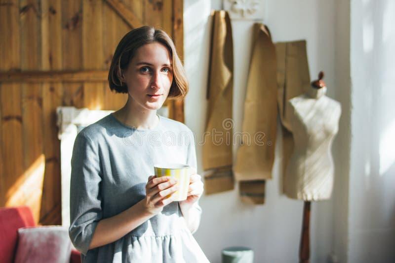 简单的灰色礼服的年轻女人有黄色杯子的坐椅子在书刊上的图片演播室,全长画象 库存图片