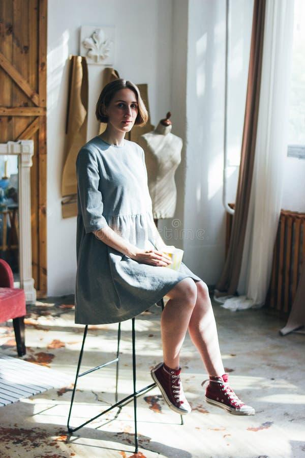 简单的灰色礼服的年轻女人有黄色杯子的坐椅子在书刊上的图片演播室,全长画象 免版税库存图片