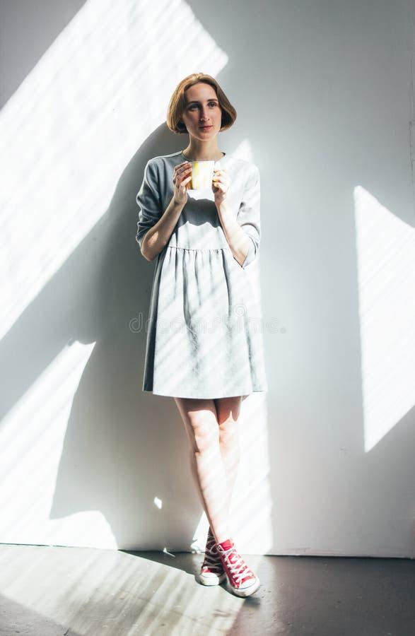 简单的灰色礼服的年轻女人有黄色杯子身分的对墙壁,全长画象,坚硬光 免版税库存照片