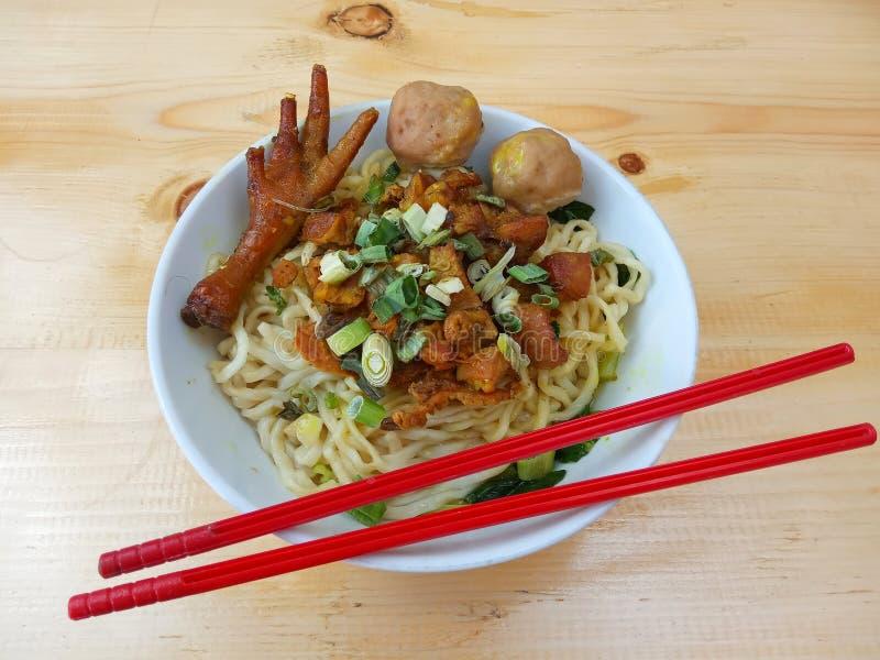 简单的照片、平的位置、可口米氏Ayam ceker、鸡汤面在白色碗和红色塑料筷子在木桌上从indo 图库摄影