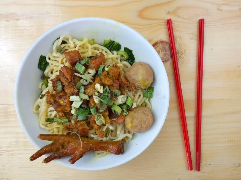 简单的照片、平的位置、可口米氏Ayam ceker bakso、鸡汤面在白色碗和红色塑料筷子在木桌上为 库存图片