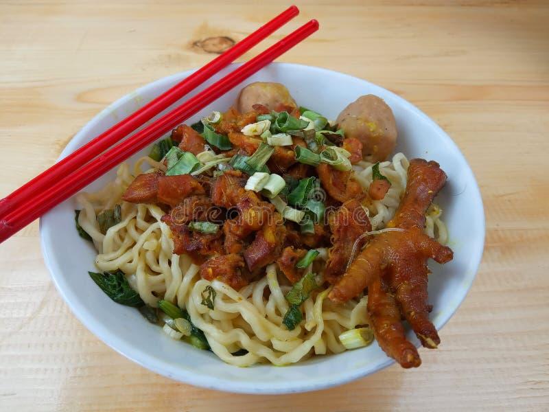 简单的照片、平的位置、可口米氏Ayam ceker bakso、鸡汤面在白色碗和红色塑料筷子在木桌上为 图库摄影