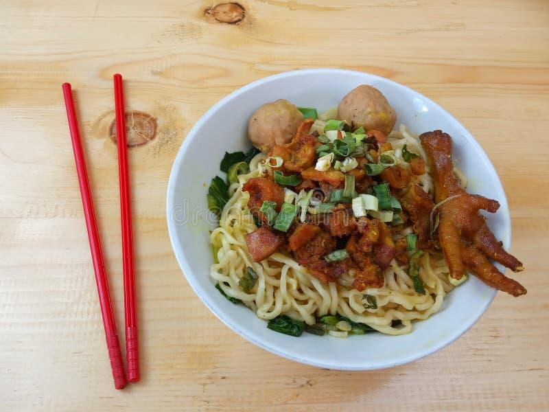 简单的照片、平的位置、可口米氏Ayam ceker bakso、鸡汤面在白色碗和红色塑料筷子在木桌上为 免版税库存图片