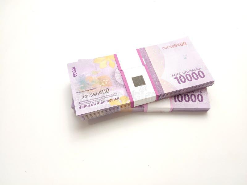 简单的照片平的位置,堆捆绑一万卢比印度尼西亚金钱,在白色背景 免版税库存图片