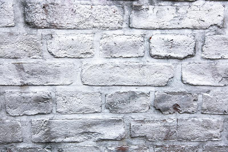 简单的白色和灰色砖墙绘与金属被喷洒的墨水油漆作为样式表面纹理背景 免版税库存照片