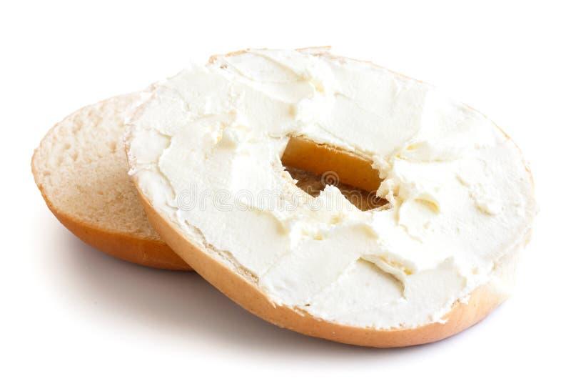 简单的百吉卷切成了两半并且传播了用乳脂干酪 被隔绝的o 库存图片