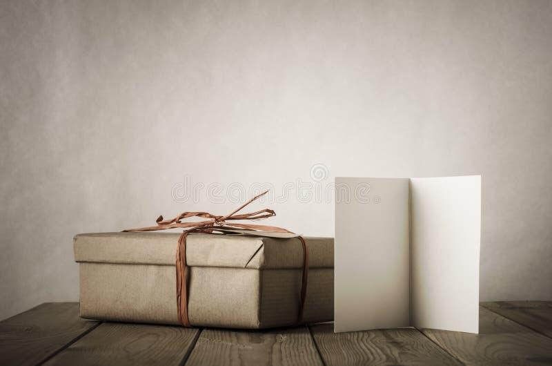 简单的礼物盒和卡片在表上 免版税库存图片