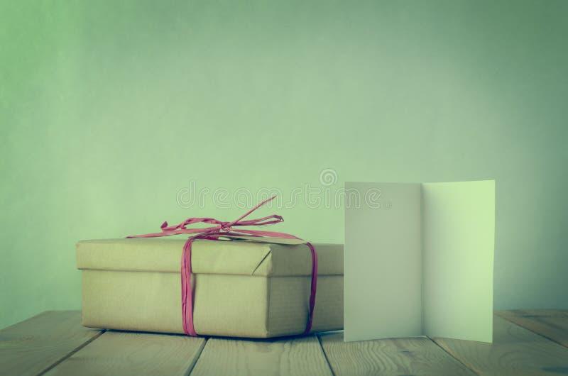 简单的酒椰有空白开放卡片的被栓的礼物盒 库存图片