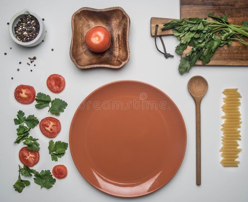 简单的食物,蕃茄,荷兰芹和penne面团,排行了白色背景,顶视图舱内甲板位置 免版税库存照片